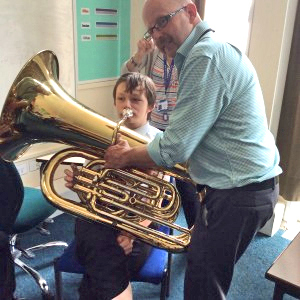 Deaf young person being assisted to play the tuba by a brass teacher