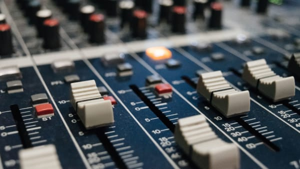 Close up of a mixing desk. Photo taken by Alexey Ruban (@intelligenciya) on Unsplash