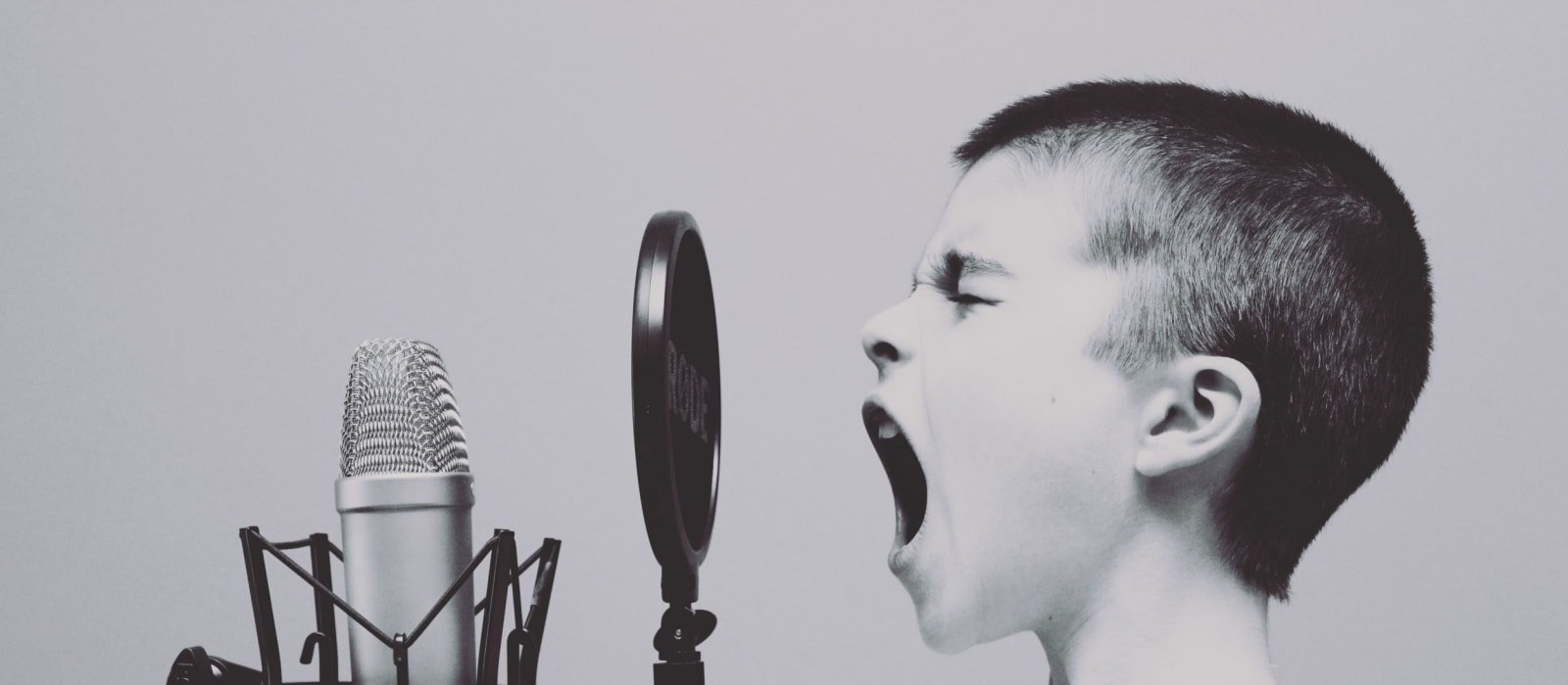Boy singing loudly into a microphone. Photo by @jasonrosewell on Unsplash