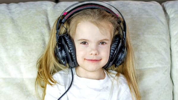 Little girl wearing big headphones (photo by @bermixstudio on Unsplash)