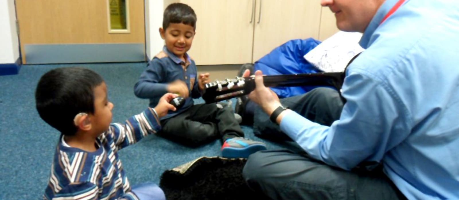 Andrew Cleaton playing the guitar with Habib, who is hearing impaired