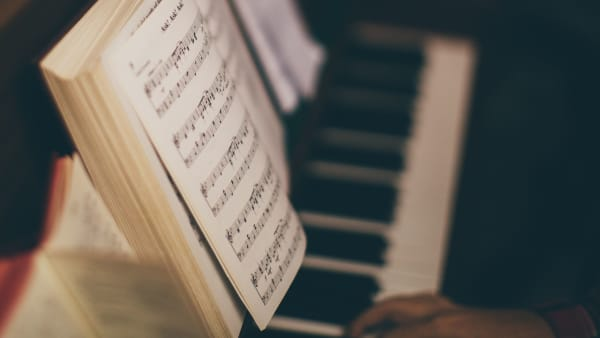 A hand plays a piano with two books of music resting on the pianos stand. Photo by Louis Smith (@zion_photo) on Unsplash