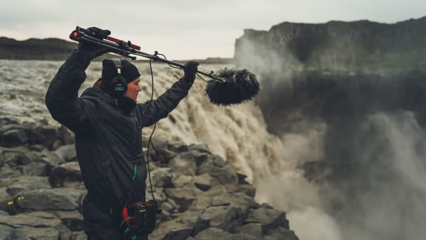 A sound recording being by a man in outdoor gear taken near the top of a waterfall (photo by @freetousesoundscom on Unsplash)