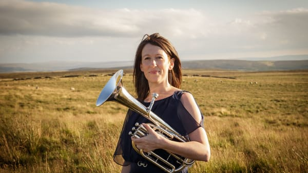 Helen Varley with her horn on the moors at sunset