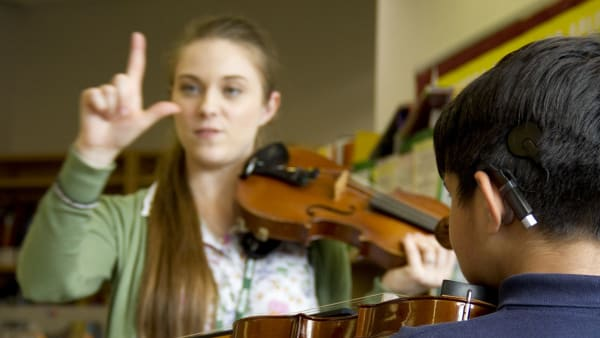 Eloise Garland (Deaf musician) teaching a hearing impaired child how to play the violin